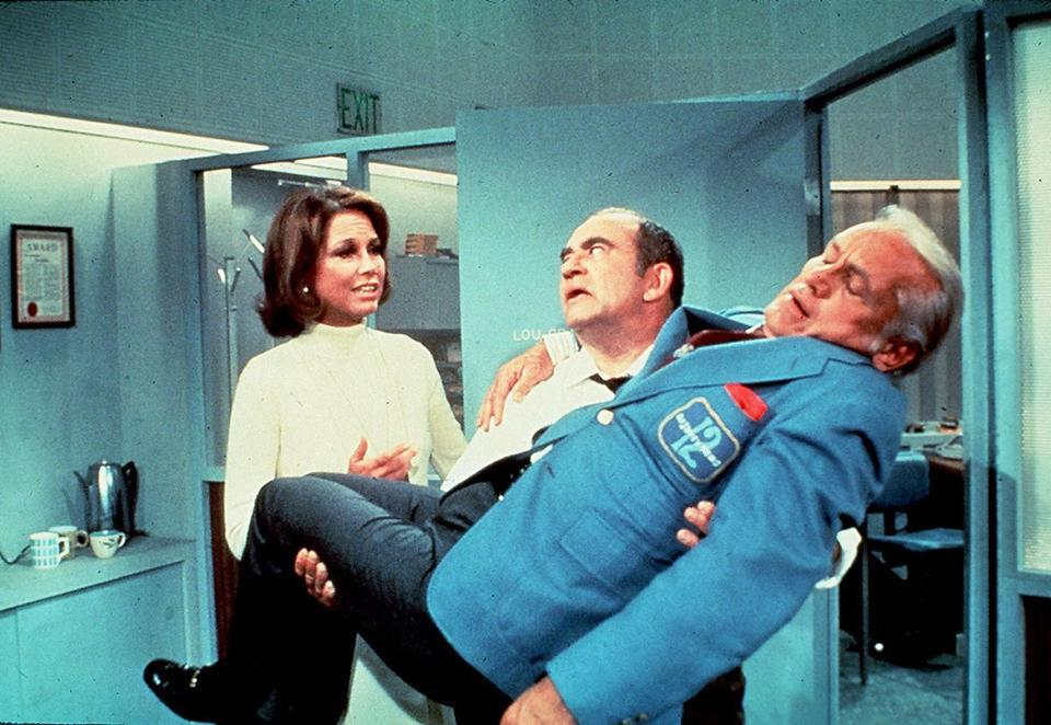 "Mary Tyler Moore, Ed Asner (center), and Ted Knight in the hit 1970s  sitcom ""The Mary Tyler Moore Show."""
