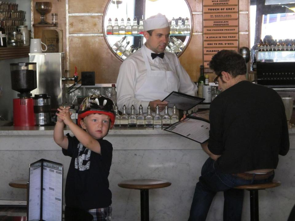 A young patron awaits a treat at The Ice Cream Bar Soda Fountain, a retro store in San Francisco's Cole Valley neighborhood, its bar a 1930s relic bought on eBay.