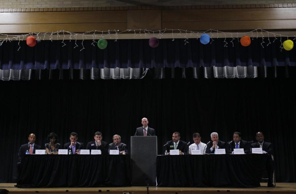 Mayoral candidates (from left) John Barros, Charlotte Golar Richie, Michael Ross, John Connolly, Bill Walczak, Felix Arroyo, Marty Walsh, Daniel Conley, Rob Consalvo, and Charles Yancey flanked moderator Chad D'Entremont (at podium) at the Edward Brooke Charter School in Roslindale.