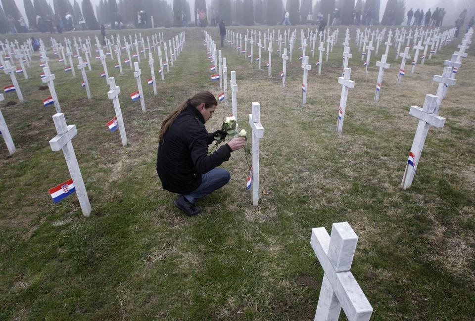 A man laid flowers on a cross in Vukovar, Croatia, where 264 people were massacred at a hospital in 1991.