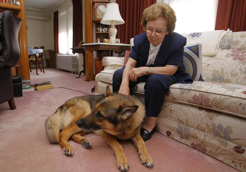 Helen Fahey, with guide dog Fletch at home in Arlington, has been reading books in Braille (inset at left) since the seventh grade.