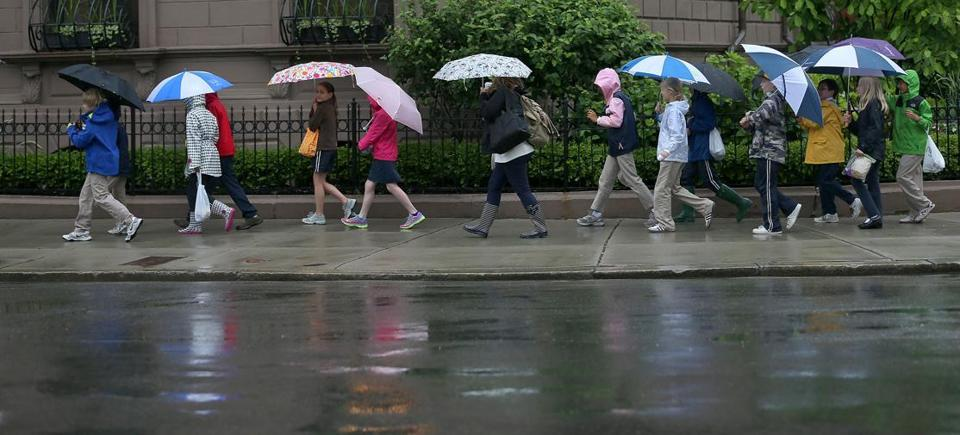 A group of young students braved heavy rain as they navigated along Arlington Street in Boston Friday. Skies were expected to clear Saturday afternoon.