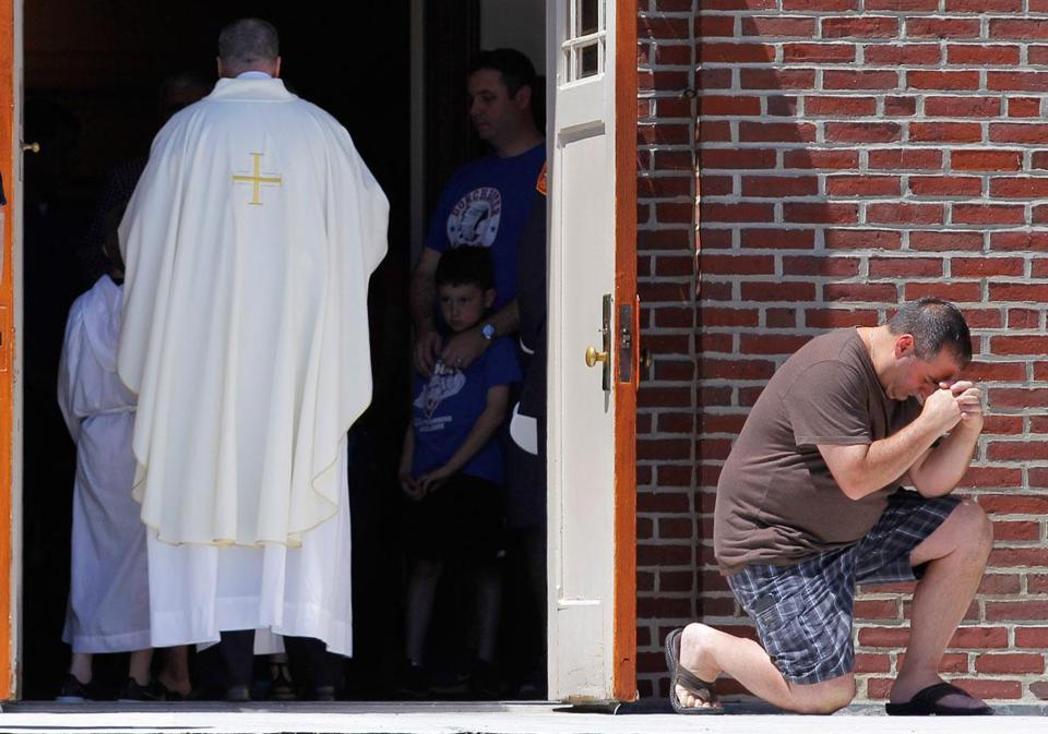 Kenny Blasi of Dorchester knelt after receiving communion during Sunday's Mass for Martin Richard at St. Ann Church.