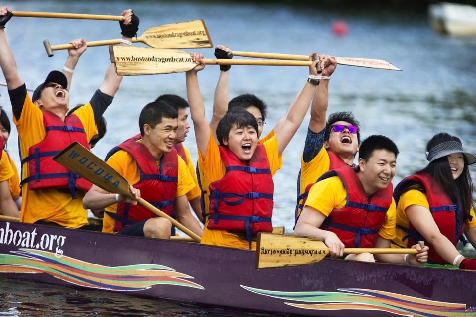 Zhao Wang (center) celebrates with her teammates on the Chinese Young Professionals after crossing the finish line at the Boston Dragon Boat Festival on the Charles River.