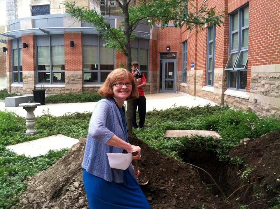 Quincy High history teacher Jane Lundquist shovels dirt onto the time capsule buried at the school.