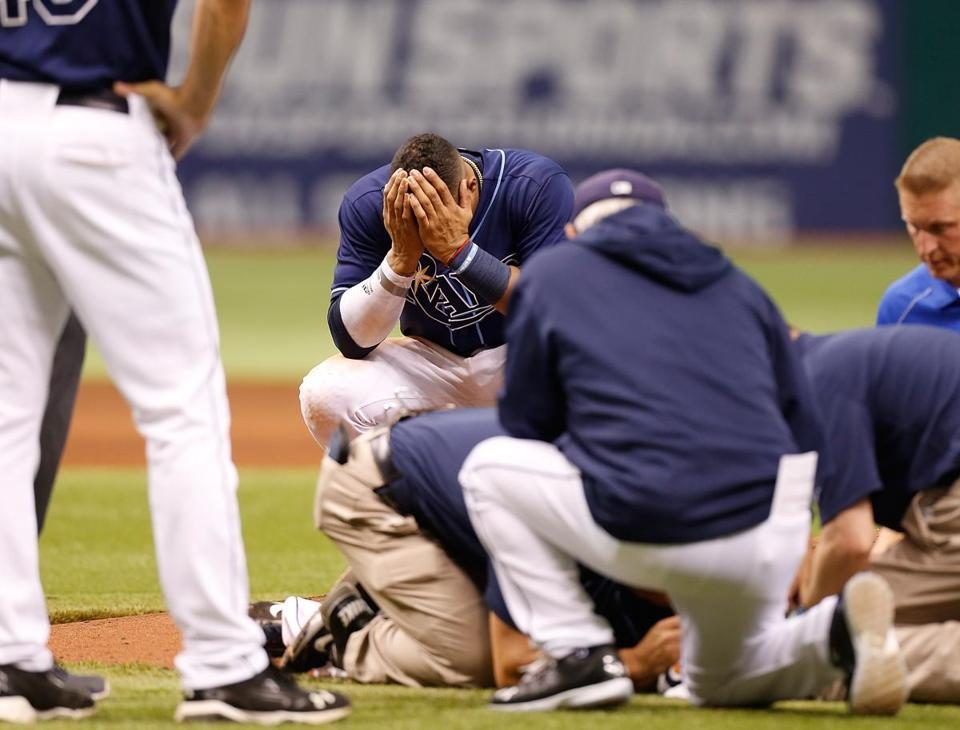 Yunel Escobar (back) is stunned after Alex Cobb was hit by a line drive. The Rays said Cobb has a mild concussion.