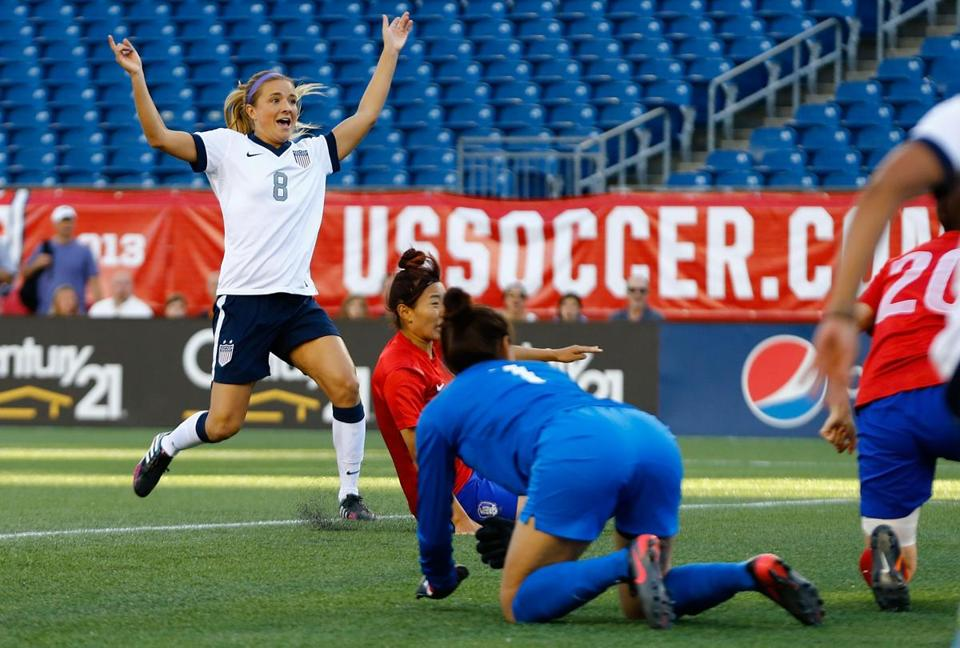 Kristie Mewis celebrates after beating South Korea goalkeeper Kim Jungmi (kneeling) in the first half.
