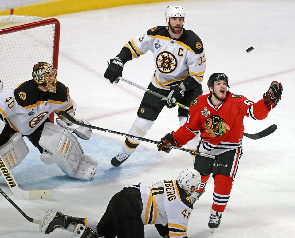 Zdeno Chara (33) and Dennis Seidenberg try to prevent the Blackhawks' Andrew Shaw from getting control of the puck in front of goalie Tuukka Rask during the Bruins' Game 2 win.