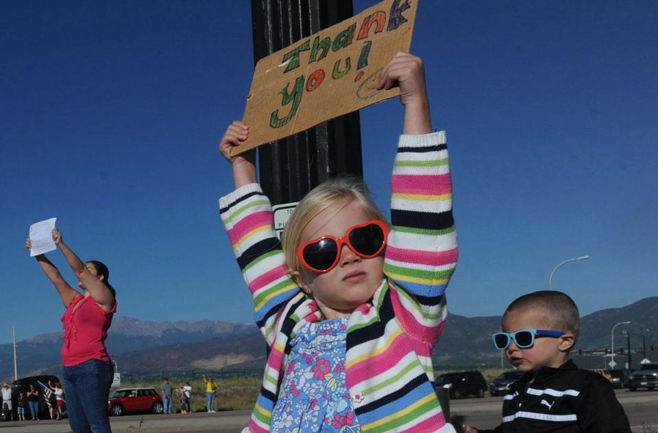 Macey Roth, 4, cheered on firefighters Sunday morning as they drove past a fire camp in Colorado Springs. Crews hope to have the wildfires fully under control by Thursday.