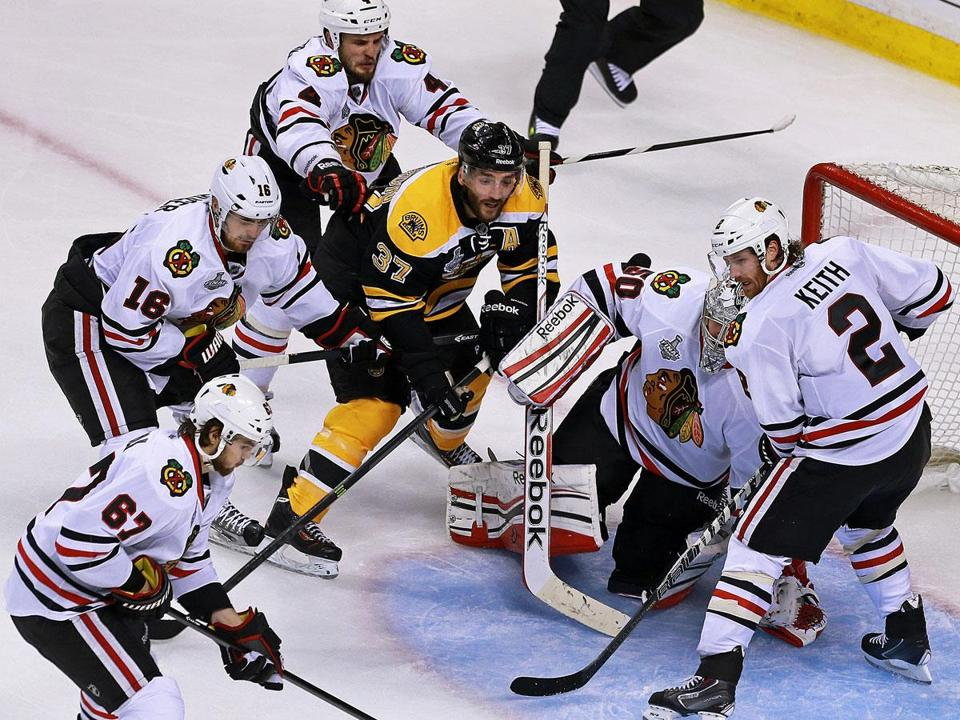 Patrice Bergeron takes his place in front of the Chicago net, drawing the attention of four Blackhawks skaters.