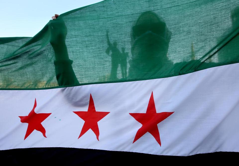 A Syrian activist behind a revolutionary flag during a protest in Beirut in May.