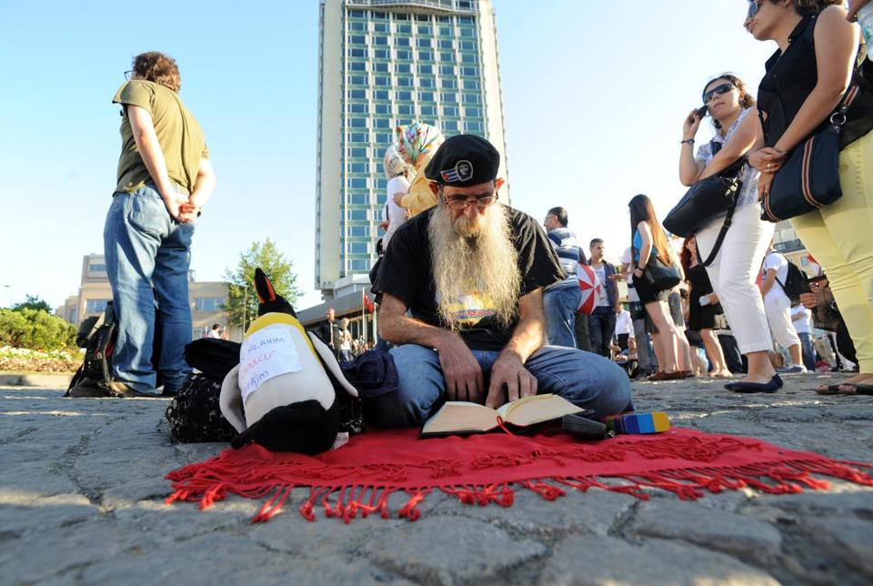 A man read during a silent antigovernment protest held in Istanbul's Taksim Square on Wednesday.