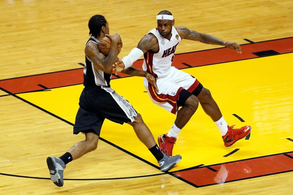 Kawhi Leonard of the Spurs tries to play keep away from LeBron James of the Heat in the first quarter of Game 6 of the NBA Finals.