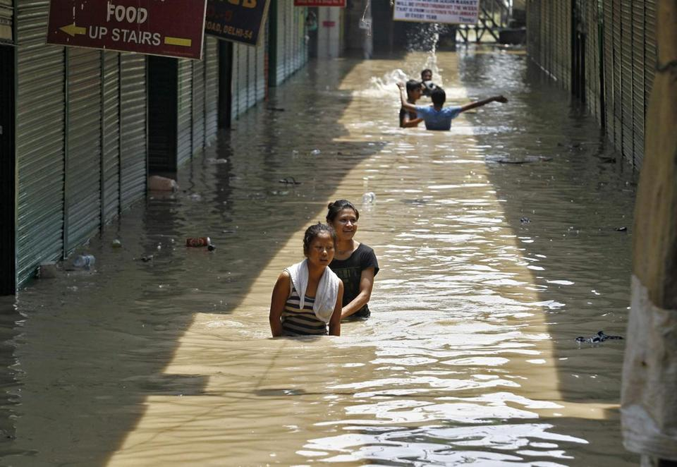 Girls waded through a flooded alley in New Delhi Thursday after heavy rains caused the Yamuna River to rise.