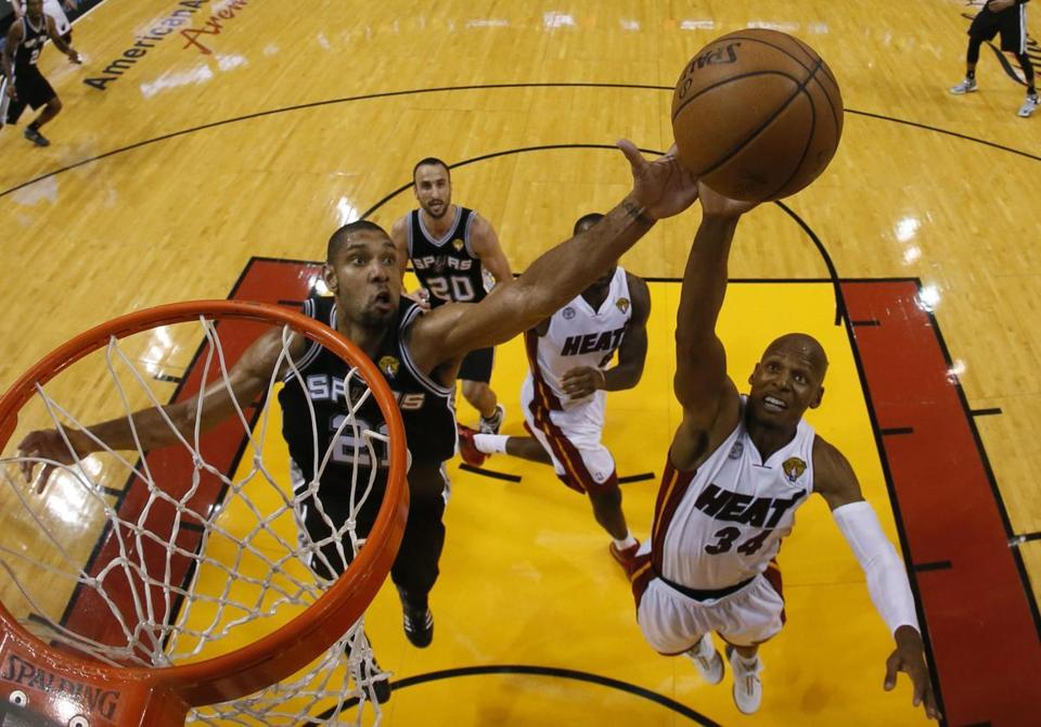 San Antonio Spurs player Tim Duncan (L) goes for a rebound against Miami Heat player Ray Allen.