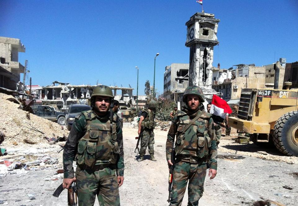 Syrian government soldiers stood in front of the clock tower flying the national flag in the main square of the city of Qusayr, in Syria's central Homs province, on June 5, after the army claimed it had seized total control of it and the surrounding region.