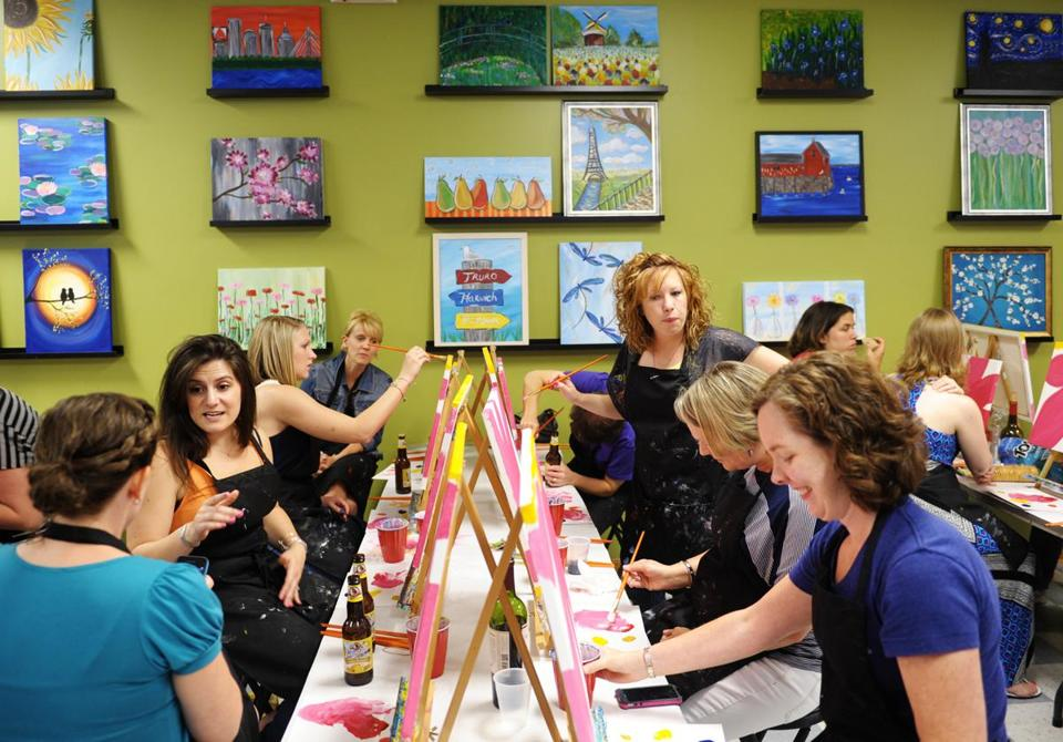 A group of women attend a painting class at Paint 'n Pour in Maynard, part of the growing trend of galleries where people can socialize.