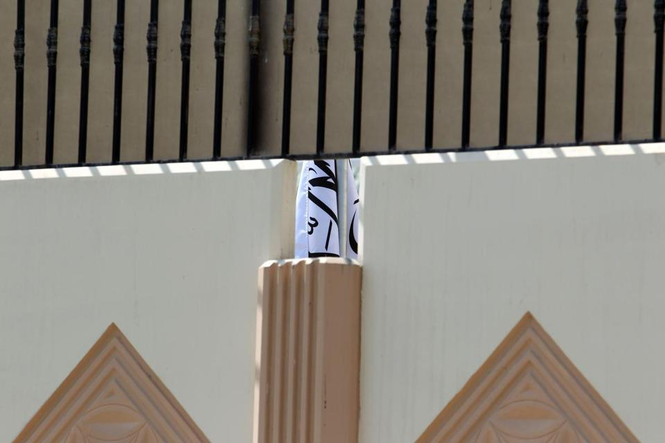 The Taliban flag was visible through a gap in a wall of the new Afghan Taliban office in Doha, Qatar, on Thursday.