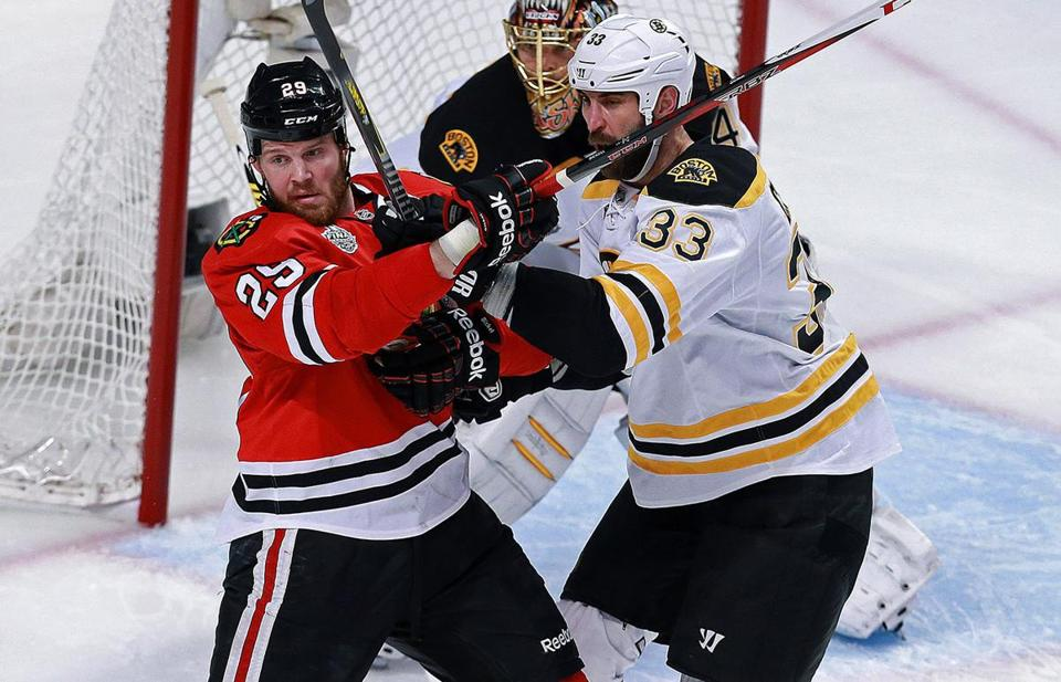 Bruins defenseman Zdeno Charamixes it up with Bryan Bickell, trying desperately to keep the ice in front of goalie Tuukka Rask clear of Blackhawks.