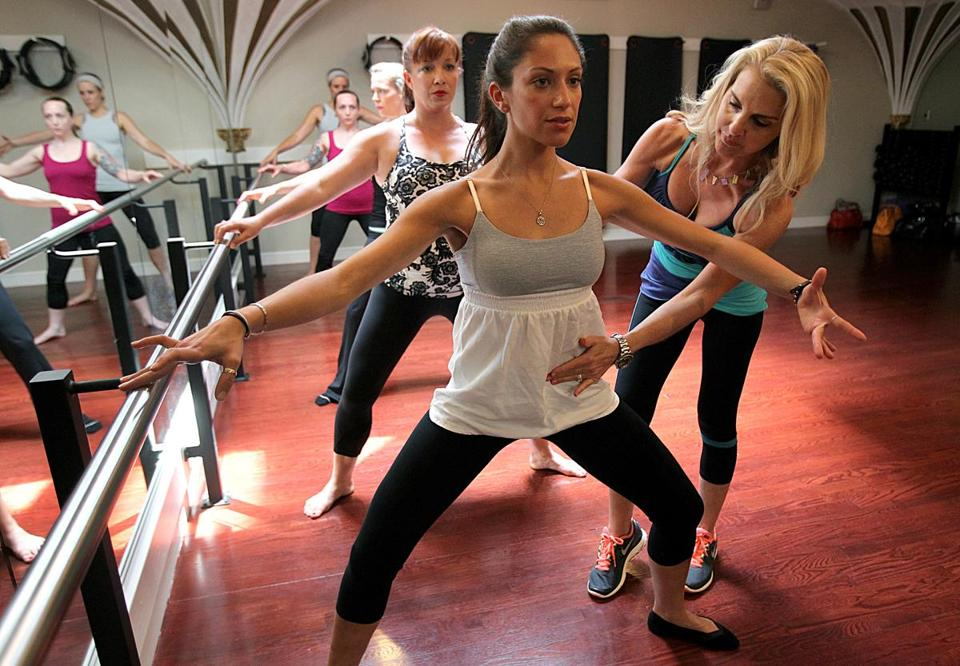 Instructor Zayna Gold works with Danae Gil de Rubiois during a barre class at Boston Body Pilates.