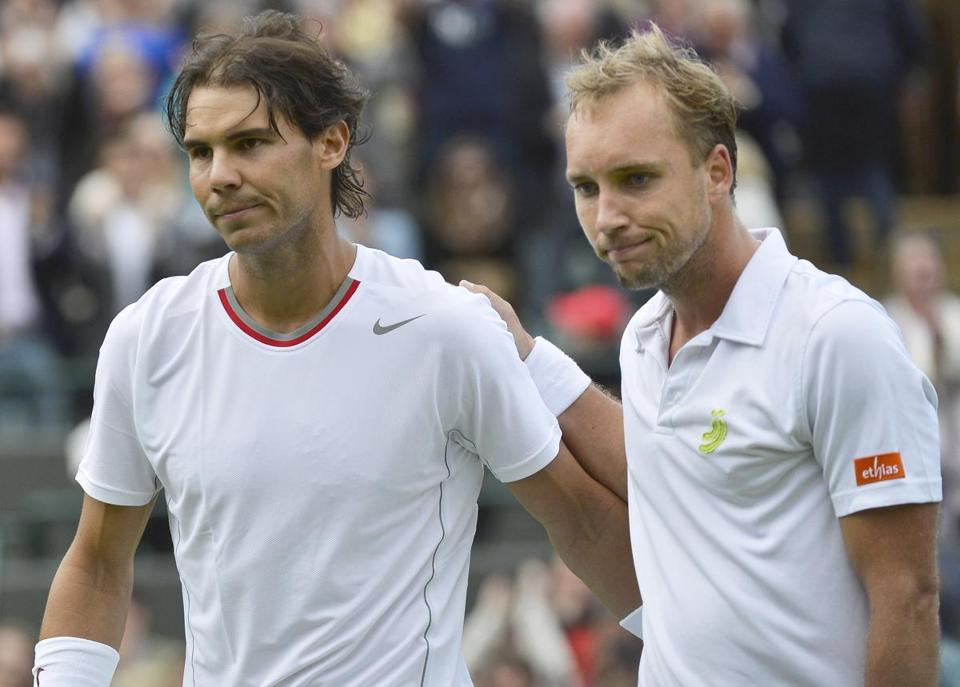 Rafael Nadal (left) walks off the court after losing to Steve Darcis at Wimbledon. Nadal had been 34-0 in the first round of Grand Slam events.
