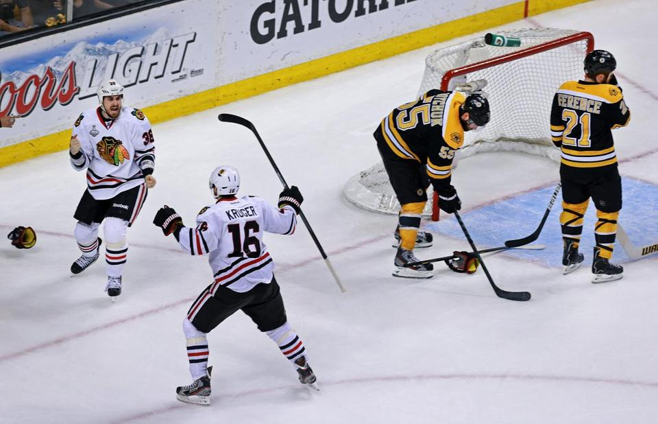 Chicago's Dave Bolland and Marcus Kruger while Boston's Johnny Boychuck and Andrew Ference shrink away after the game-clinching goal.