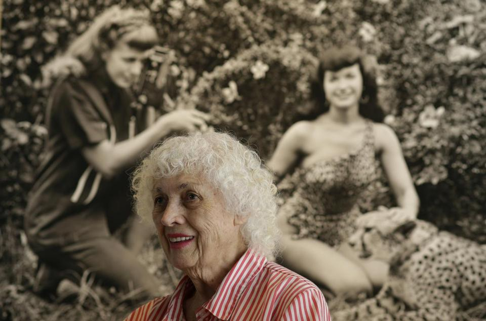 Bunny Yeager in front of a picture of her photographing Bettie Page in 1954.