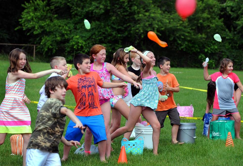 Children get their opponents wet during Pembroke's Great Water Balloon Fight on Tuesday, including Cara Clifford, 5, (below) who nervously bit down on one of her balloons before the conflict started.