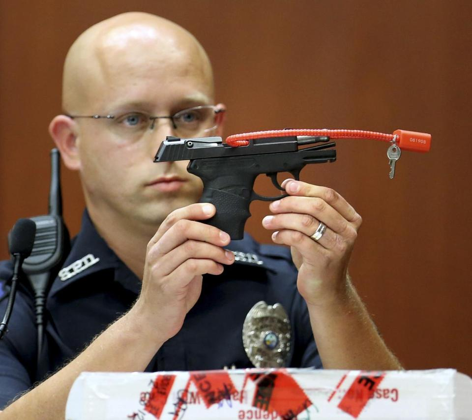During court testimony, Sanford police Officer Timothy Smith held up the gun used to shoot Trayvon Martin.