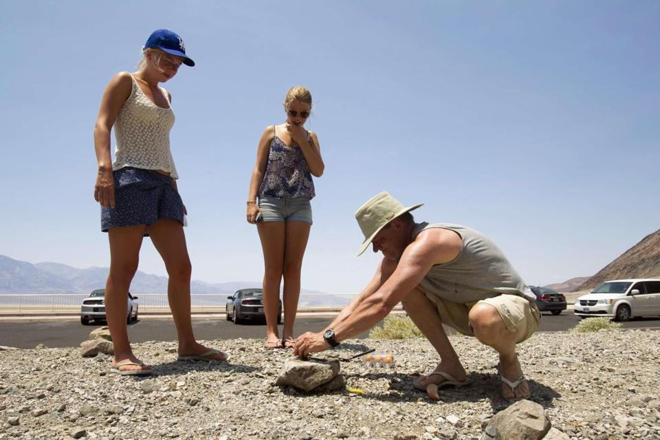 Emilia Kristoffersson (left) 19, and her sister Ella, 15, of Sweden, watched their father, Bengt Johsson, try to fry an egg on a rock at Badwater Basin in Death Valley National Park.