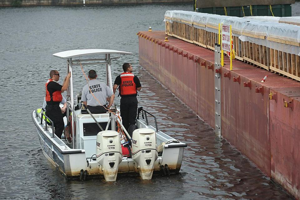 State Police inspect the fireworks barge Monday.
