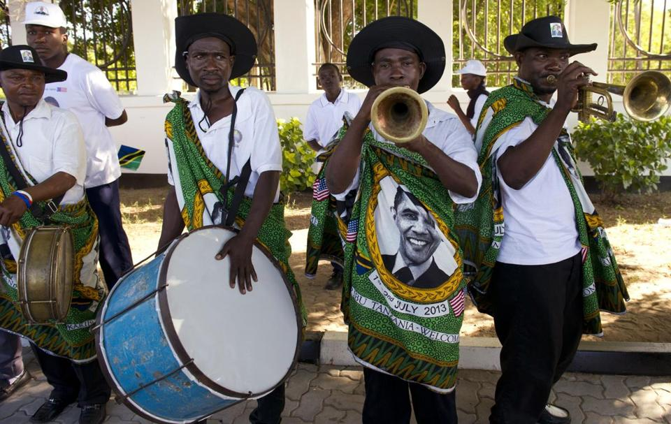 Bandmembers in khangas with President Obama's image performed as the US leader arrived in Dar Es Salaam, Tanzania.