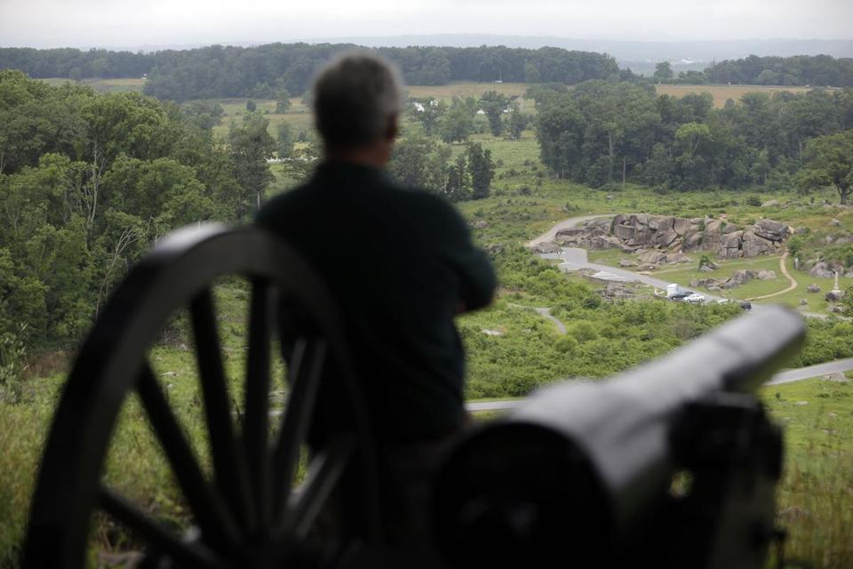 A visitor to Little Round Top views Devil's Den during ongoing activities commemorating the battle.