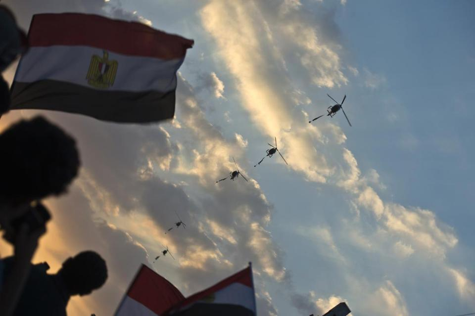 Egyptian army helicopters fly over as hundreds of thousands of Egyptian demonstrators gathered outside the presidential palace in Cairo during a protest calling for the ouster of President Morsi.