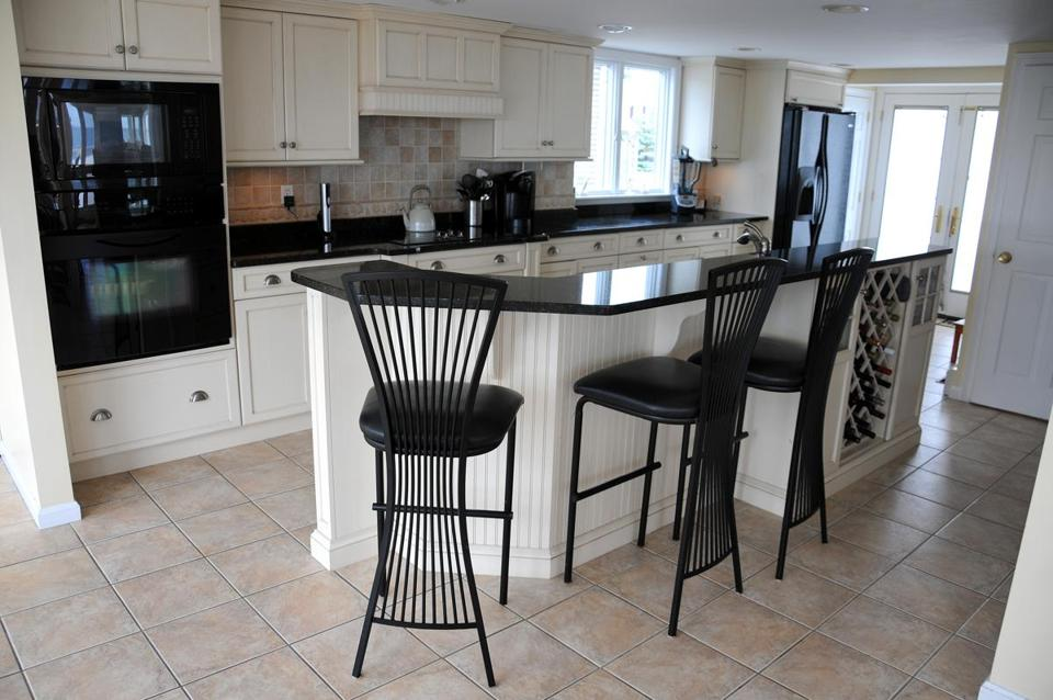 The kitchen has black granite counters and flows into the living room.