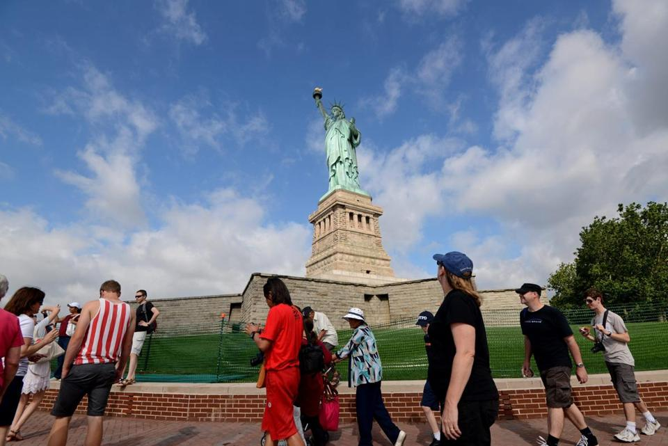 Hundreds of tourists arrived at the Statue of Liberty on Thursday after its reopening to the general public months after significant damage to Liberty Island from Hurricane Sandy.
