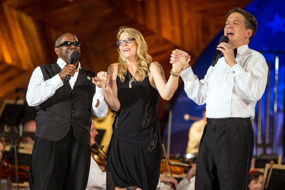 From left, Ellis Hall, Susan Tedeschi, and Keith Lockhart joined hands on stage at the Hatch Shell at the Boston Pops Fireworks Spectacular.