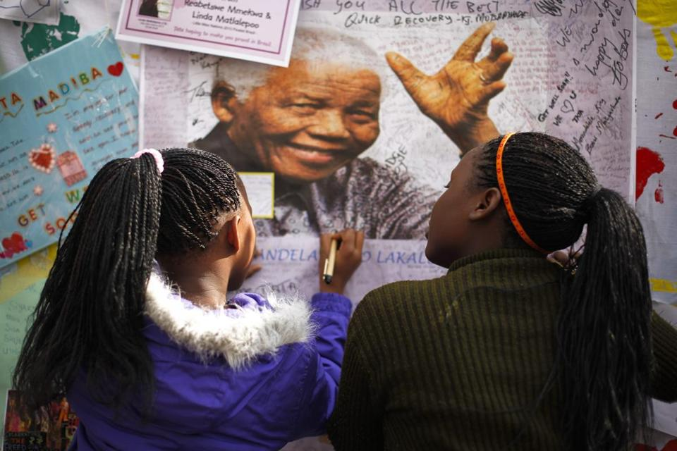 Well-wishers wrote messages on a portrait of Nelson Mandela outside the Pretoria hospital where he is a patient.