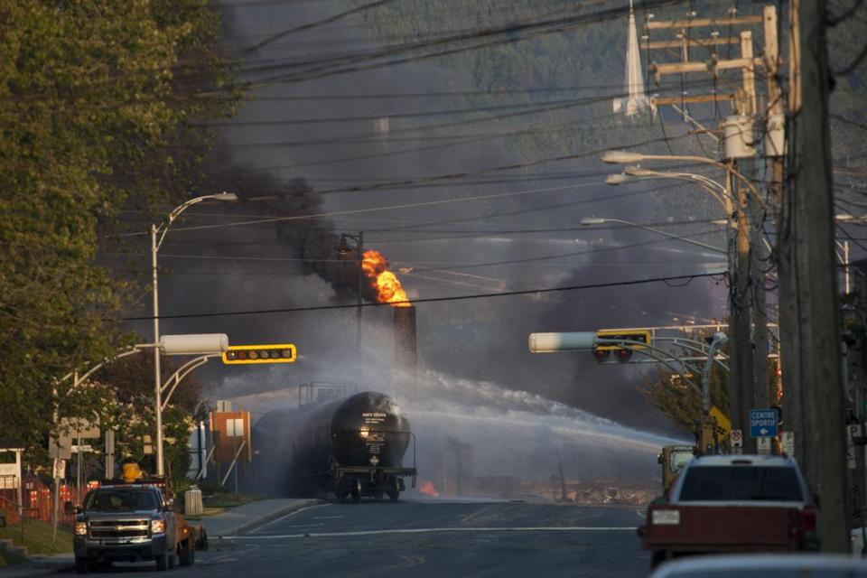 Firefighters doused a blaze after a freight train loaded with oil derailed, sparking explosions that engulfed about 30 buildings in fire.