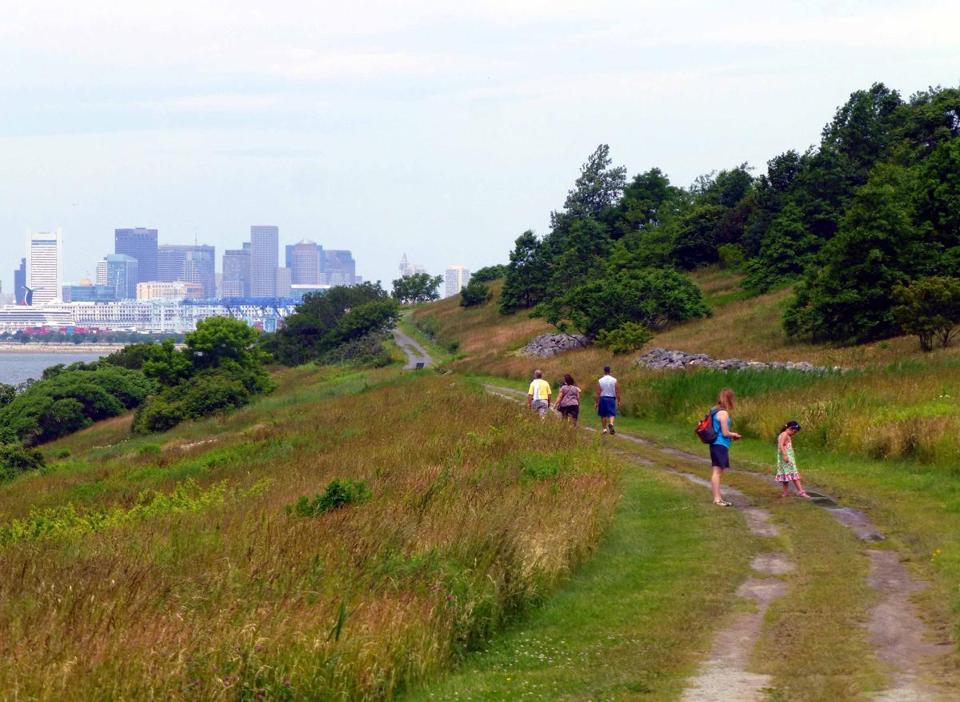 Visitors enjoy spectacular views as they walk the trails at Spectacle Island. (Patricia Harris for The Boston Globe)