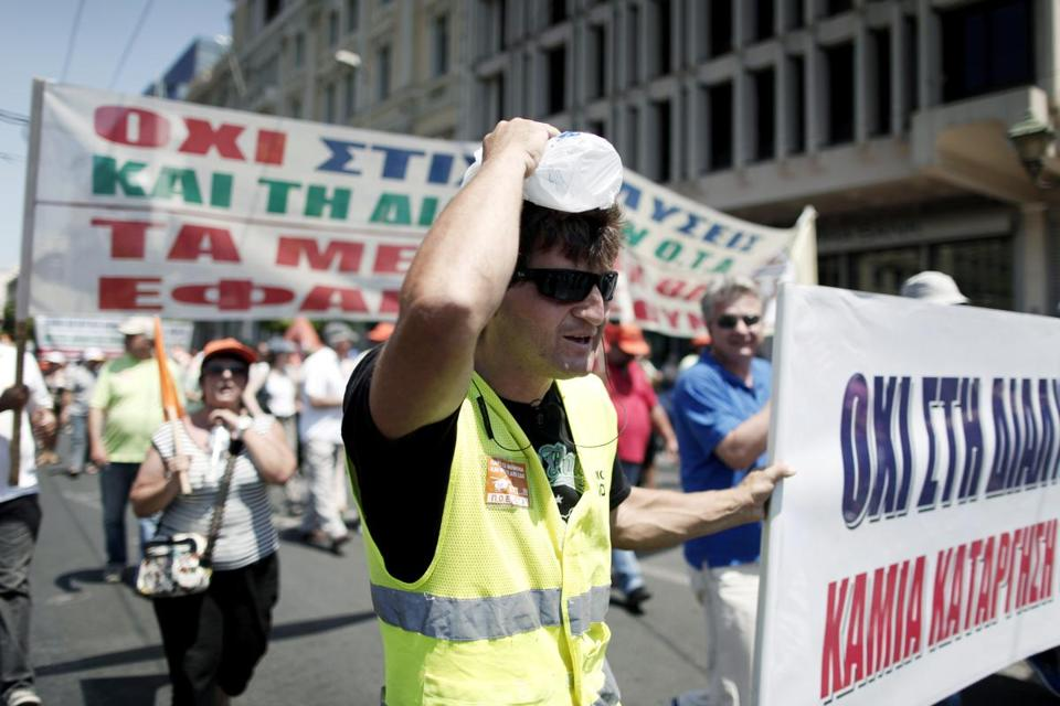 A striking municipal worker used a bottle of water to cool himself during a protest in Athens Tuesday.