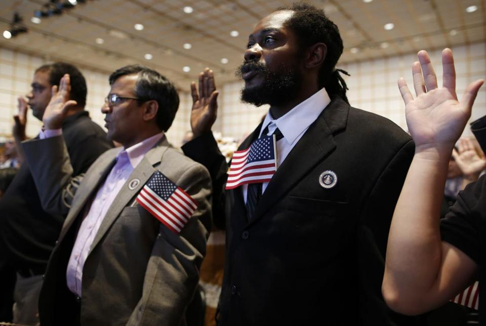 Ramon Aquino (left ), Lax Iyer, and Jermaine Green were among the people who took the oath of citizenship Wednesday at the JFK library in Dorchester.