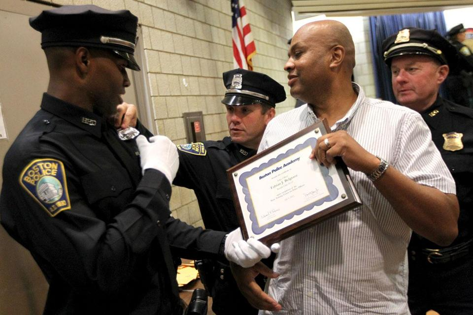 Fabian J. Belgrave (left) was congratulated by his mentor, Boston police Detective Larry Ellison (with plaque), following Belgrave's graduation Tuesday from the Boston Police Academy.