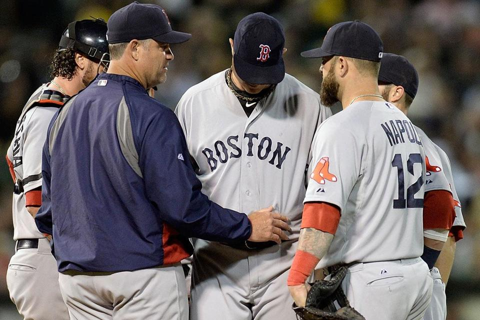 Manager John Farrell gives Jon Lester a pat after pulling the starter in the seventh inning. Lester dropped to 8-6.