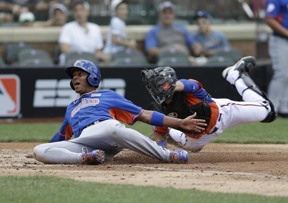 The World team's Xander Bogaerts, a Red Sox prospect, scores ahead of the tag of the US' Austin Hedges in the Futures game in New York.