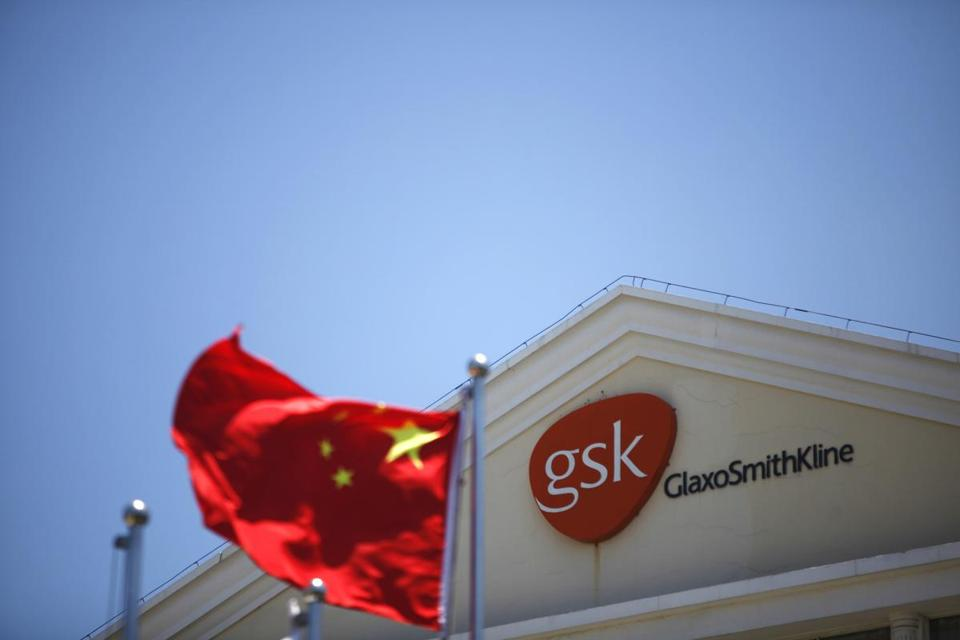 A Chinese national flag flutters in front of a GlaxoSmithKline (GSK) office building in Shanghai.