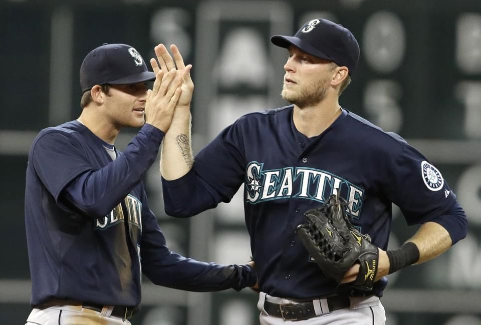 Seattle's Brad Miller (left) and Michael Saunders celebrated the Mariners' 4-2 win over Houston on Saturday night.