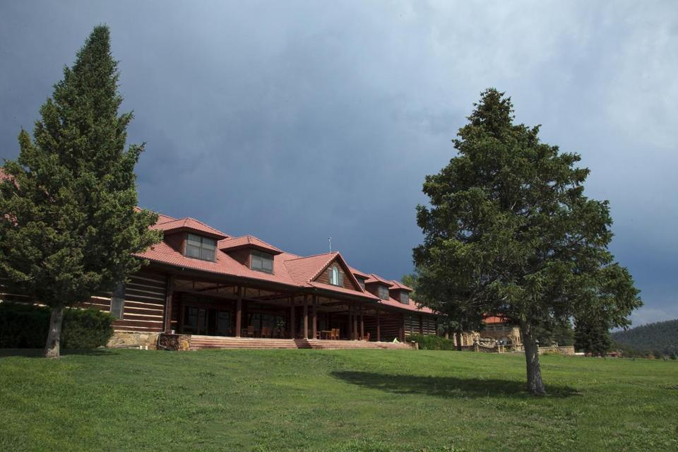 The main building and one of the guides  surveying the expanse at Vermejo Park Ranch in New Mexico. The preserve Ted Turner created for hunters and fishermen is now open to guests.