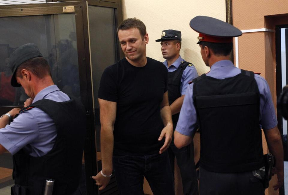 Alexei Navalny (center) left a glass-walled cage during a court hearing on Friday.