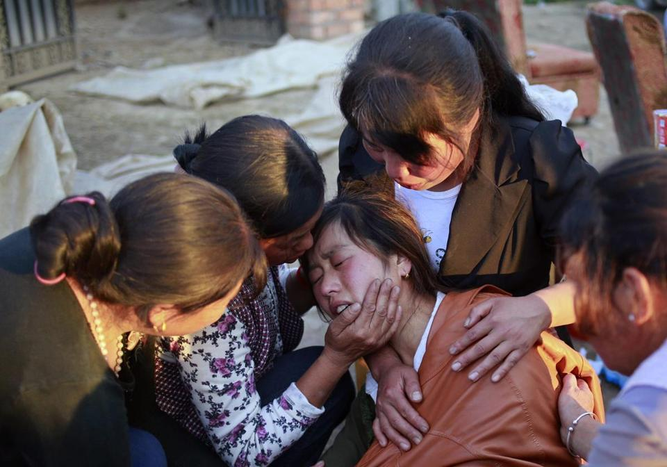 Family members consoled a woman who lost her daughter in Monday's earthquake near the city of Dingxi. Officials said more than 600 people were injured.